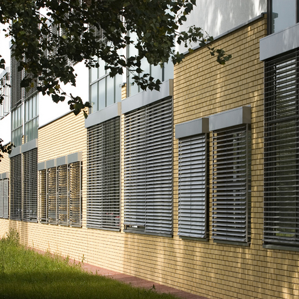 grey venetial blinds on many windows yellow building