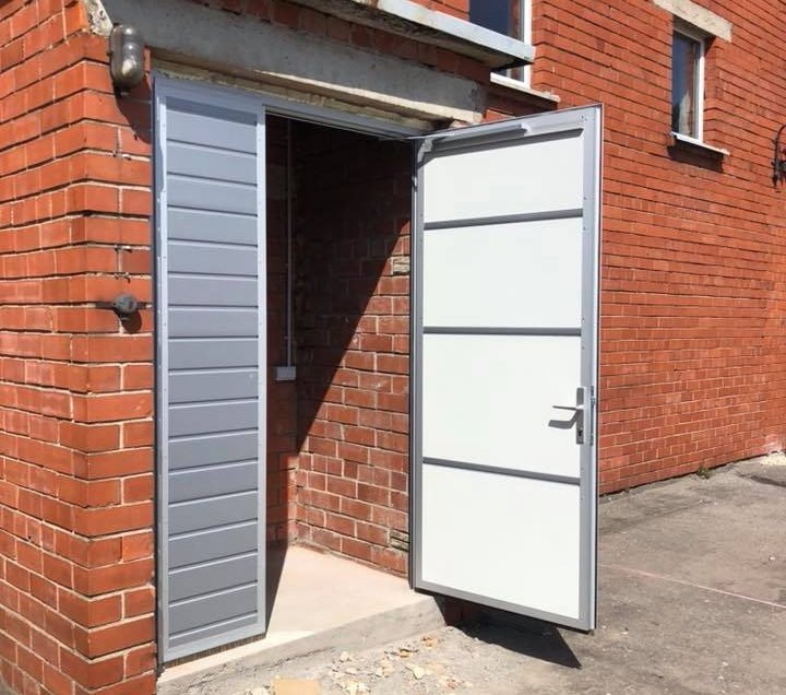open entrance door double leaf door metallic panels white and silver colour red brick building